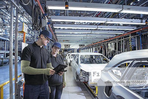 Auszubildende inspizieren Autos am Fließband in einer Autofabrik