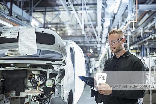 Ingenieur mit digitalem Tablett am Fließband in einer Autofabrik
