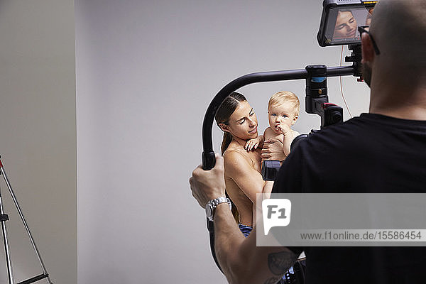 Photographer taking portrait of mother and baby