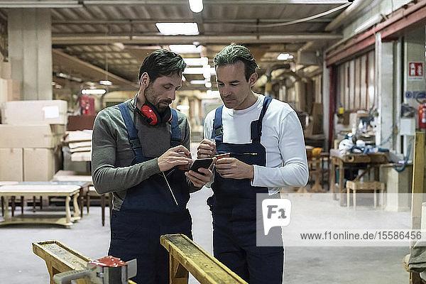 Arbeitnehmer benutzen Smartphone während der Kaffeepause in der Fabrik