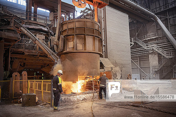 Steelworkers testing pour of molten steel from ladle in steelworks
