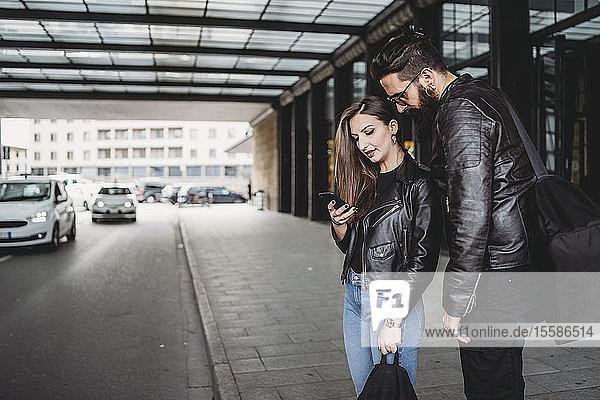Ehepaar mit Smartphone außerhalb der Station