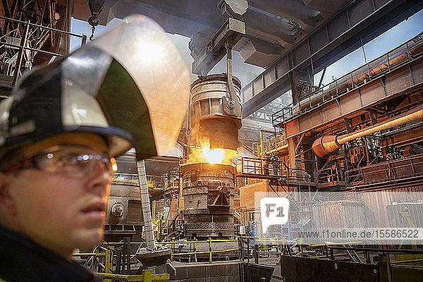 Auszubildender Stahlarbeiter im Vordergrund beim Gießen von geschmolzenem Stahl im Stahlwerk