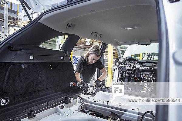 Arbeitnehmerin bei der Montage von Autoinnenteilen am Fließband in einer Autofabrik