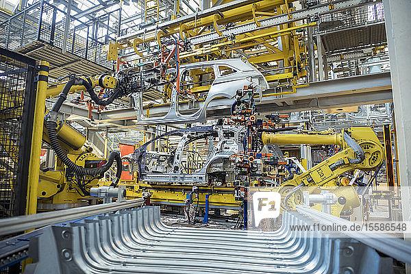 Roboter mit Autokarosserie in der Produktionslinie einer Autofabrik