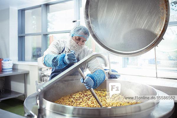 Arbeiter rührt eine Charge Lebensmittel in einer Lebensmittelfabrik um