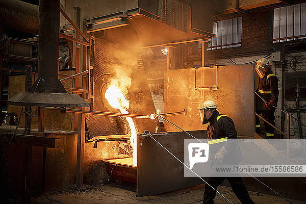 Workers pouring liquid titanium alloy from furnace in titanium recycling plant