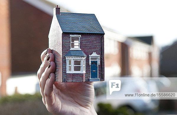 Teenagerin  die ein von einem Mann angefertigtes Modell eines Hauses vor einer Wohnsiedlung hält  seichter Fokus  Nahaufnahme der Hand