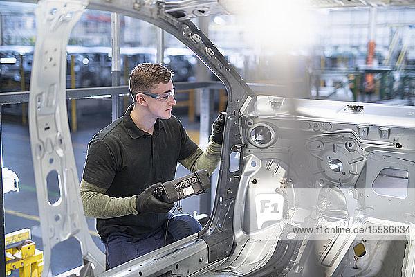 Ingenieur testet Autokarosserie in Autofabrik