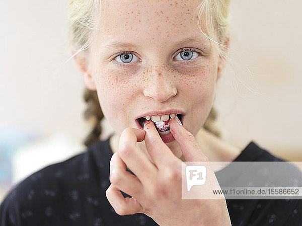 Girl baking a cake  eating fresh raspberry in kitchen  head and shoulder portrait