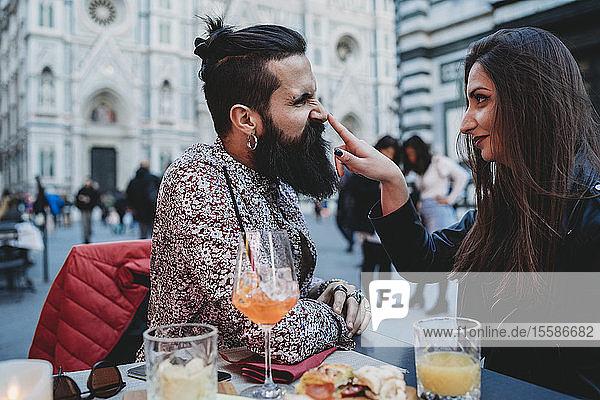 Frau klopft spielerisch auf die Nase eines Mannes im Café  Santa Maria del Fiore  Florenz  Toskana  Italien
