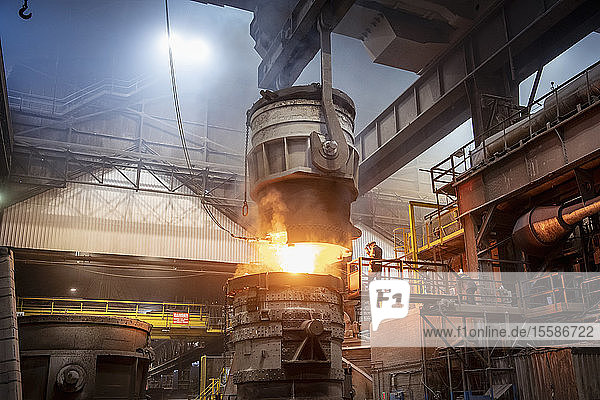Steelworkers pouring molten steel in steelworks