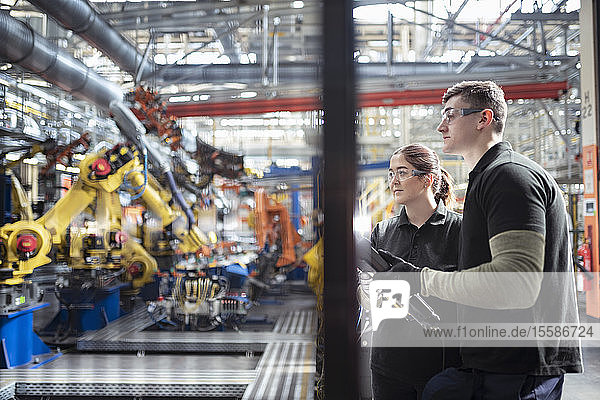 Apprentice engineers programming robots in car factory