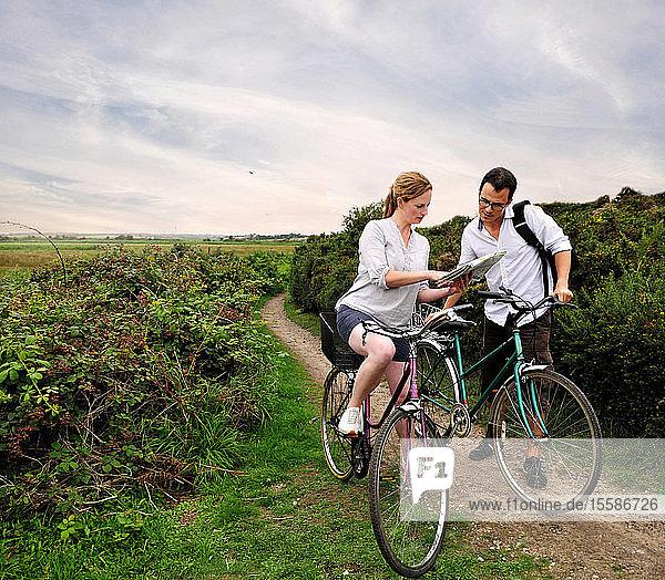 Mittleres erwachsenes Radfahrerpaar auf ländlichem Feldweg mit Blick auf die Karte  Southwold  Suffolk  UK