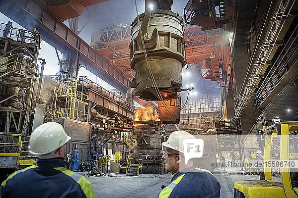 Stahlarbeiter  die in Stahlwerken geschmolzenen Stahl in Vakuumformen gießen