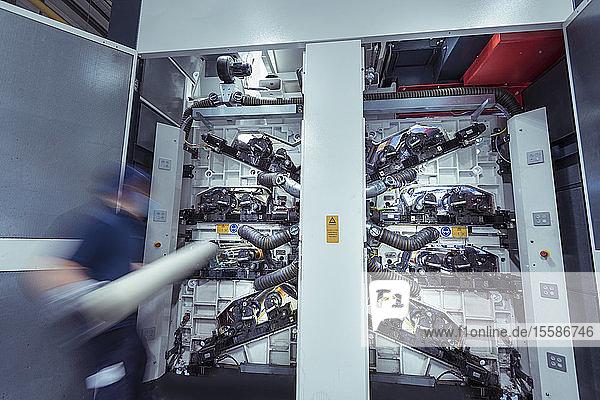 Arbeiter beim Einsetzen von Druckwalzen in die Druckmaschine in der Druckerei  Bewegungsunschärfe