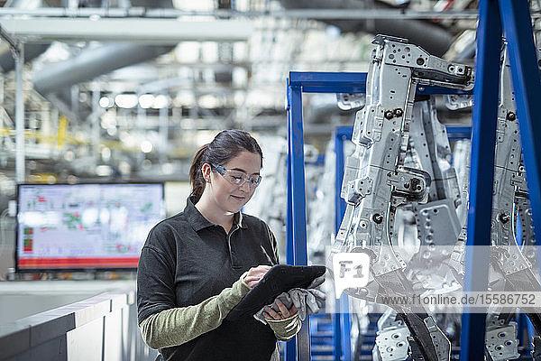 Ingenieurin in Ausbildung verwendet digitales Tablett zur Inspektion von Teilen in Autofabrik