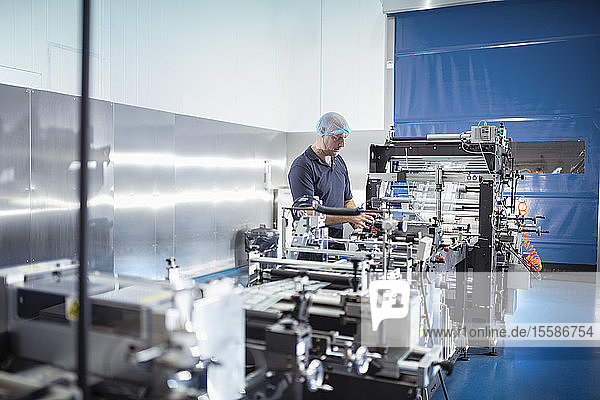 Worker with food packaging machine in print factory