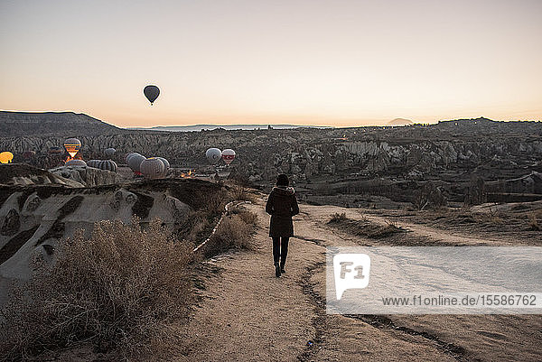 Frau geniesst Ansicht und Darstellung von Heissluftballons im Tal  Göreme  Kappadokien  Nevsehir  T�rkei
