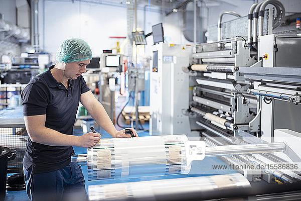 Arbeiter schreibt Notizen auf neu bedruckter Lebensmittelverpackung in Druckerei