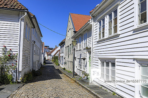 Beautiful old town  cobbled street  flowers and white wooden houses  blue sky in summer  Gamle Stavanger  Rogaland  Norway  Scandinavia