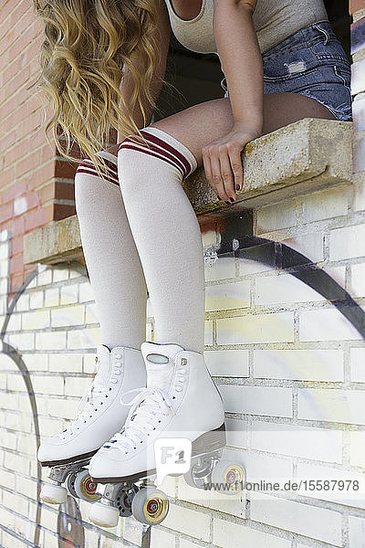Young blond woman wearing roller skates