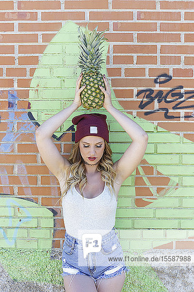 Portrait of young blond woman with ananas over her head