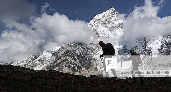 Man and woman trekking with Mt Everest  Nuptse and Kala Patthar in background  Himalayas  Solo Khumbu  Nepal
