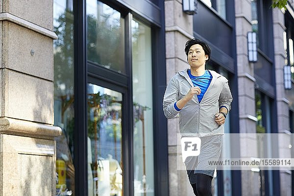 Young Japanese man running downtown Tokyo
