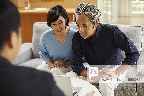 Senior Japanese couple at home with salesman