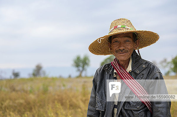 A farmer standing in a field wearing a straw hat; Taungyii  Shan State  Myanmar