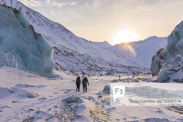 Winter hikers explore Black Rapids Glacier as the sun sets over the Alaska Range; Alaska  United States of America