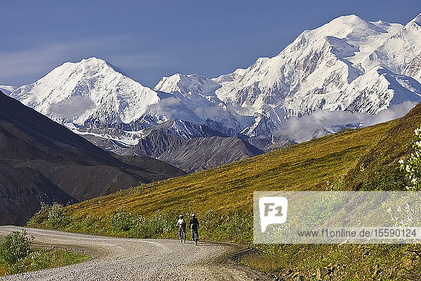 Two Women Ride Bikes Over Thorofare Pass With Mt. Mckinley In The Background In Denali National Park  Alaska