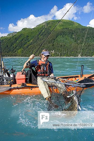 Male Fisherman Sitting On Edge Of Kayak Catching A Halibut In Resurrection Bay Seward Kenai Peninsula Alaska Summer