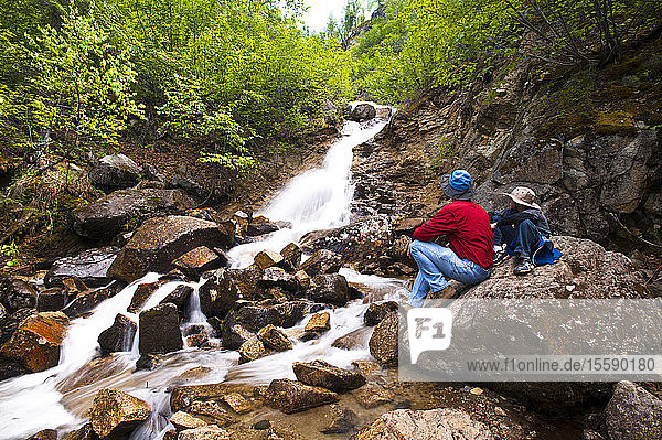 A Father And Son On A Hike Rest On A Rock While Looking At Cascade Falls Near Byers Lake In Denali State Park  Southcentral Alaska  Summer