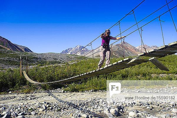 A Woman Walks On A Suspension Bridge Across College Creek To Gulkana Glacier  Southcentral Alaska  Summer/N