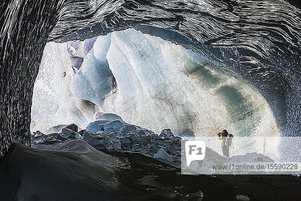 A woman takes a snapshot of Black Rapids Glacier from the entrance of an ice cave; Alaska  United States of America
