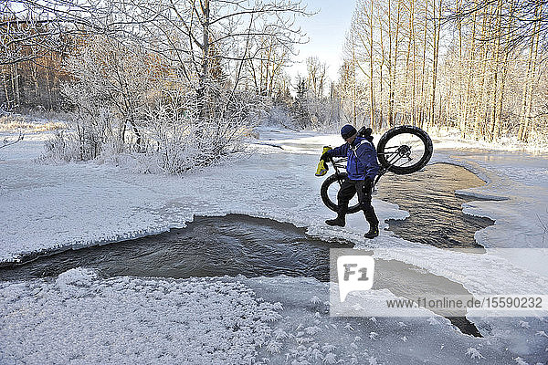 Bicyclist Crosses Open Water Of Campell Creek While Carrying A Snow Bike In Far North Bicentennial Park Near Anchorage  Southcentral Alaska  Winter