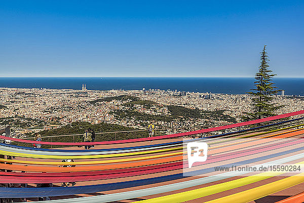 Tourists standing at a railing in Tibidabo Amusement Park overlooking the city of Barcelona and the Mediterranean Sea with a rainbow-coloured canopy in the foreground; Barcelona,  Catalonia,  Spain