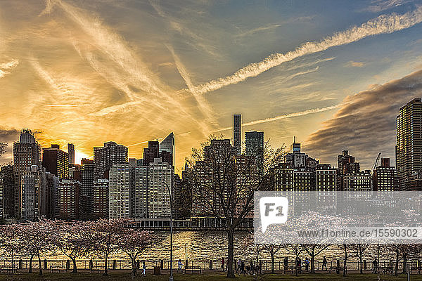 Skyline of Manhattan viewed at dusk from Roosevelt Island across the East River; New York City  New York  United States of America