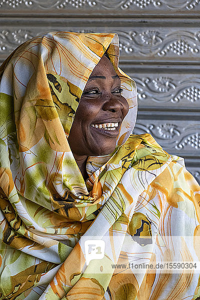 Portrait of a Sudanese woman with a big smile and colourful headscarf; Dongola  Northern State  Sudan