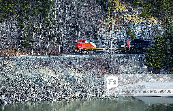 Canadian National Railway train traveling beside a lake; Terrace  British Columbia  Canada