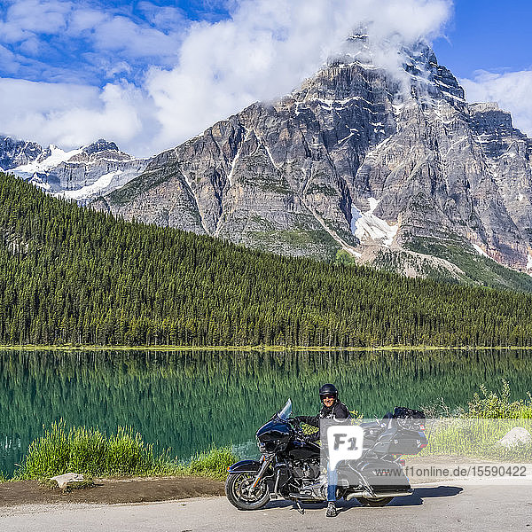 Man sitting on his motorcycle on the roadside of Icefield Parkway in front of Waterfowl Lakes; Improvement District No. 9  Alberta  Canada