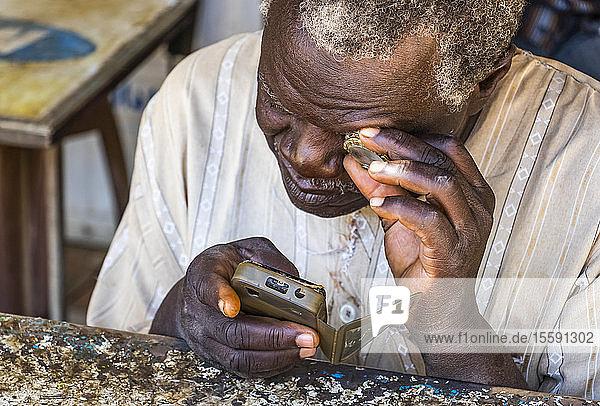 Sudanese man repairing a mobile phone; Kerma  Northern State  Sudan