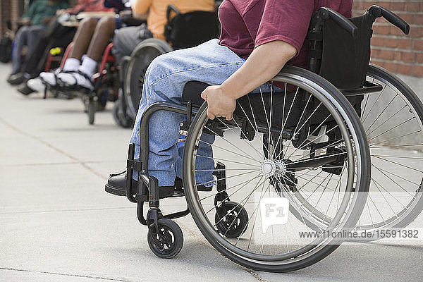 Low section view of a woman sitting in a wheelchair with Muscular Dystrophy