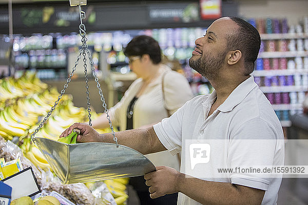 Man with Down Syndrome weighing banana in a grocery store