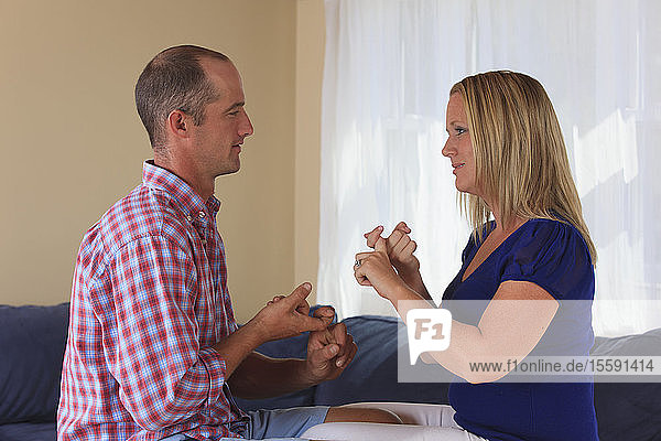 Husband and wife with hearing impairments signing 'friends' in American sign language