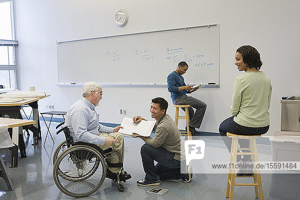 University professor with Muscular Dystrophy with his students in a classroom