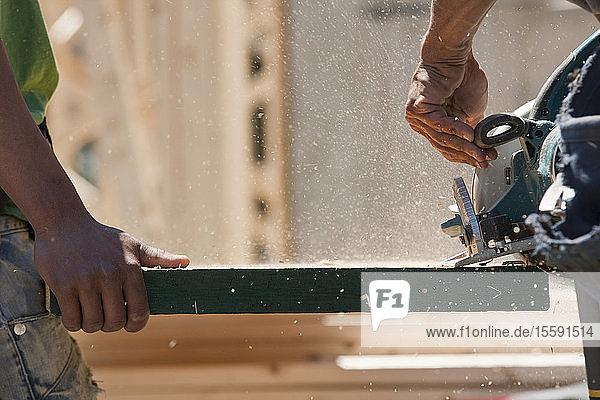 Carpenters sawing beam