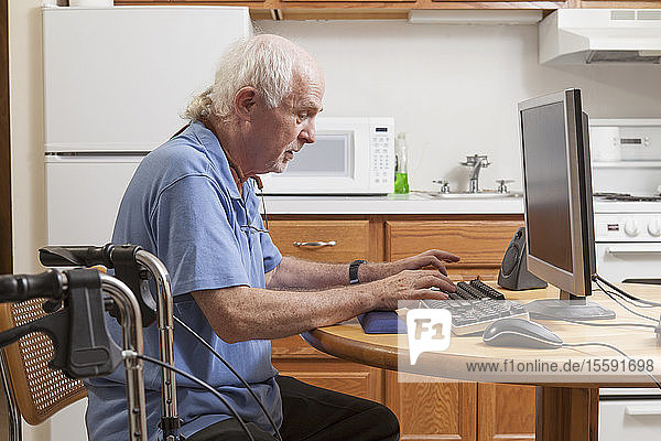 Man with Ataxia with his walker working on his computer in the kitchen